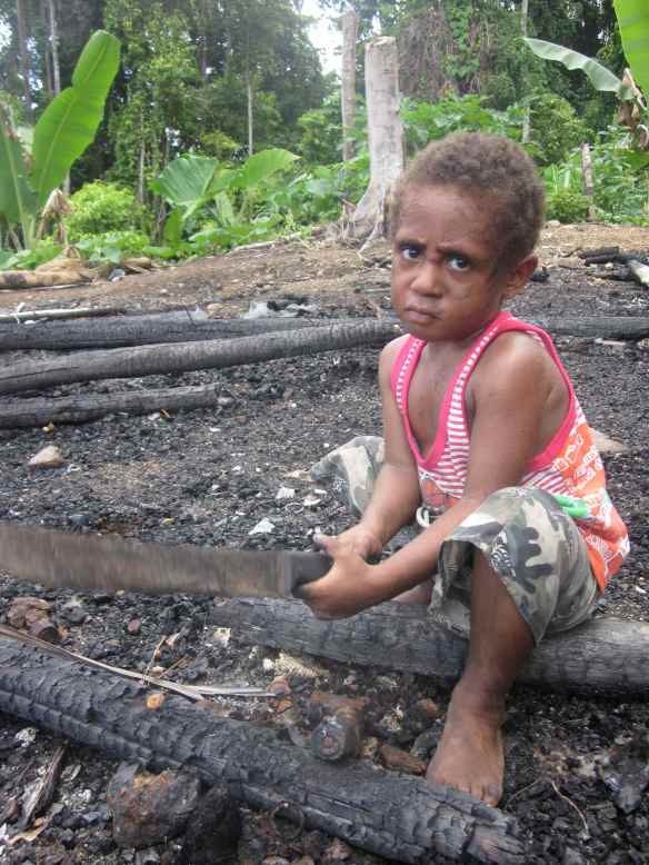 Child in the ruins of burnt Refugee village. Photo by David Fedele